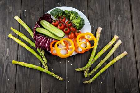 fresh vegetables on plate on rustic wooden background