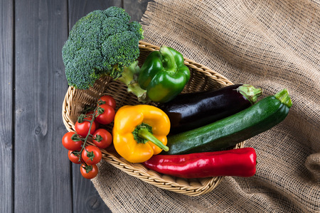 fresh seasonal vegetables in basket on rustic wooden table