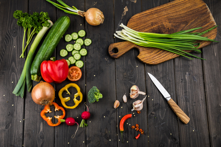 fresh seasonal vegetables and knife on rustic wooden background Banco de Imagens