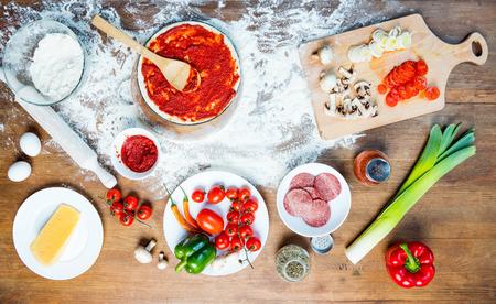 bovenaanzicht van pizza-ingrediënten, tomaten, salami en champignons