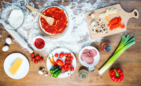 top view of pizza ingredients, tomatoes, salami and mushrooms Фото со стока