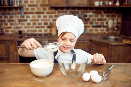 little boy pouring flour in bowl Stock Photo