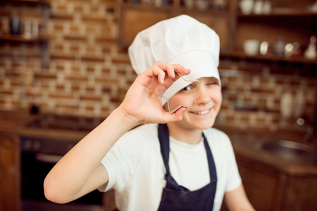 boy in chef hat holding star shaped cookie cutter