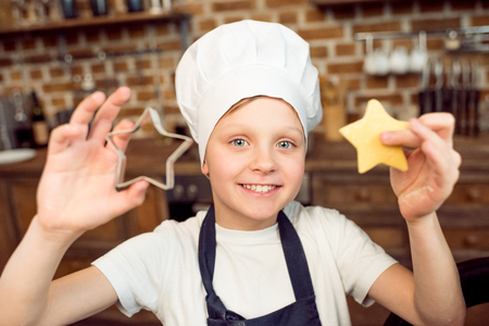 cutter: boy holding raw star shaped and cookie cutter Stock Photo