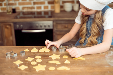 food supply: little girl in chef hat making shaped cookies in kitchen