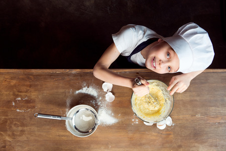 boy making dough for cookies on wooden table