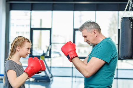 punched out: preteen girl boxing with senior trainer Stock Photo