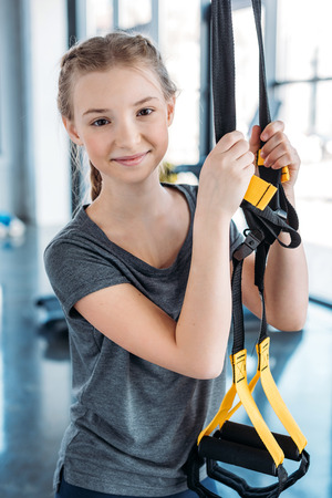 preteen girl training with resistance bands in fitness class