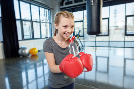 punched out: preteen girl in boxing gloves with sport bottle.