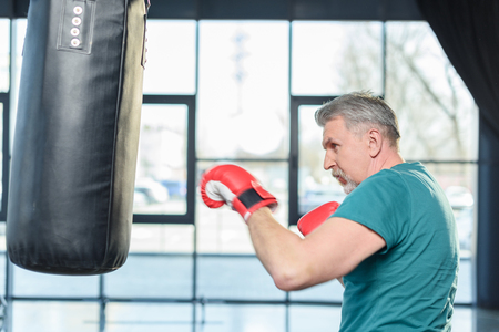punched out: senior sportsman in red boxing gloves punching bag