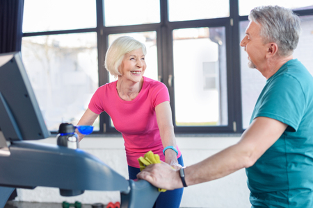old sport couple training on treadmill in fitness class