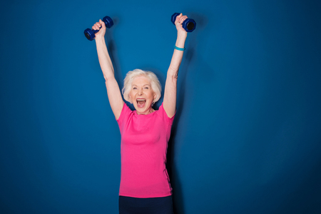 senior fitness vrouw training met halters geïsoleerd op blauw Stockfoto