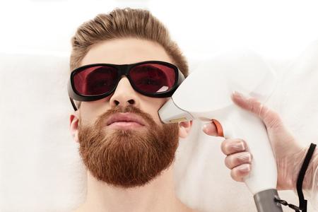 若い男が白で隔離の顔にレーザー皮膚治療を受けて