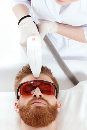 man receiving laser skin care on face. healthy lifestyle man concept Stock Photo