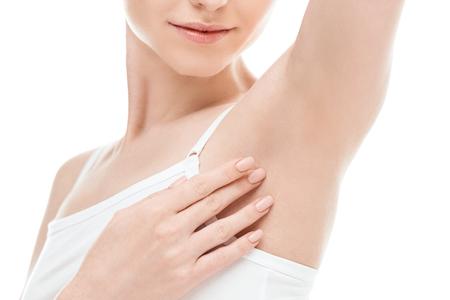 Frau zeigt Achselhöhlen isoliert auf weiß. Hautpflege Frau Konzept