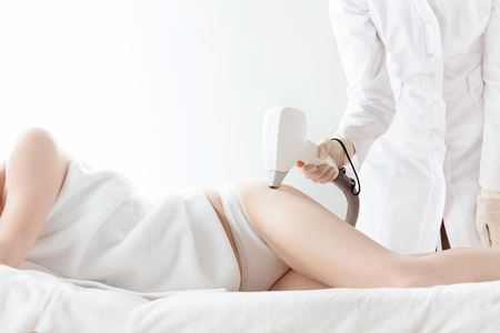 young woman lying and receiving laser skin care on hip