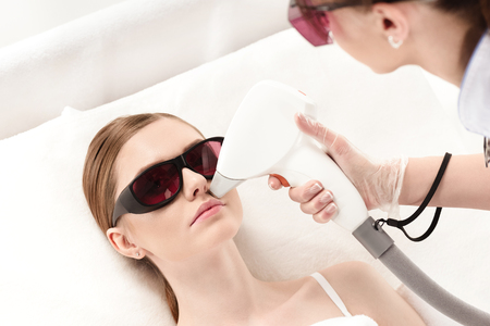 young woman receiving laser hair removal epilation on face Imagens