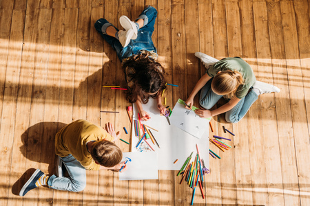 kids drawing on paper with pencils while lying on floor