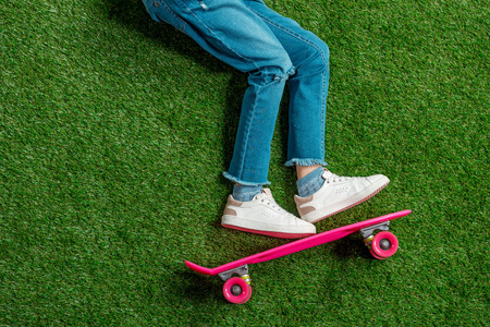 cute little girl with pink skateboard lying on green lawn
