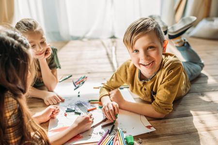 Niños Dibujando En Papel Con Lápices Mientras Está Acostado En El ...