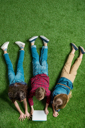 children using digital tablet while lying on grass