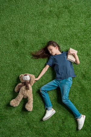 top view of little girl with teddy bear holding book while lying on grass