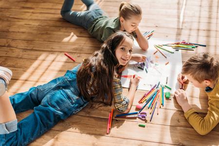바닥에 누워있는 동안 연필로 종이에 그리는 아이들 스톡 콘텐츠