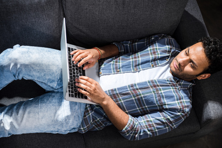 homeoffice: serious young man lying on sofa and using laptop, small business people concept