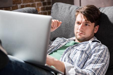 jonge man liggend op een bank en met behulp van laptop, kleine mensen uit het bedrijfsleven concept Stockfoto