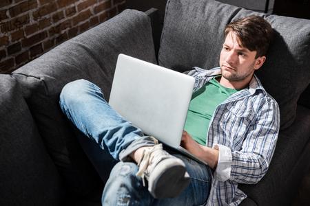 jonge man liggend op de bank en met behulp van laptop thuis, kleine mensen uit het bedrijfsleven concept