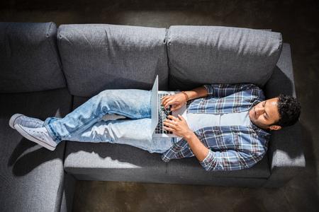 knappe jonge man liggend op een bank en met behulp van laptop, kleine mensen uit het bedrijfsleven concept