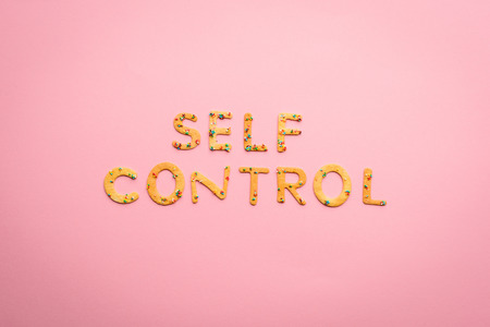 Top view of self control lettering made from sweets isolated on pink