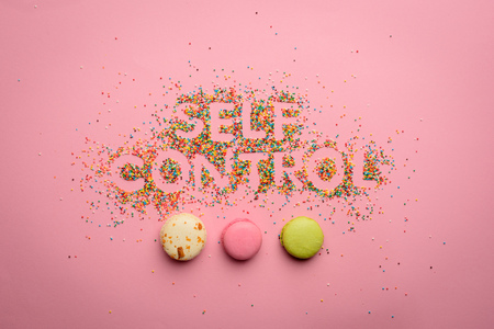 Top view of self control lettering made from candies isolated on pink 版權商用圖片