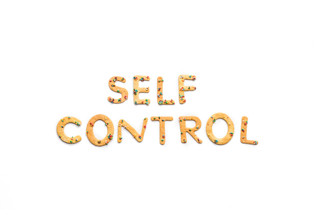 Top view of self control lettering made from sweets isolated on white