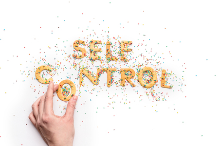 Top view of self control lettering made from sweets and hand holding letter