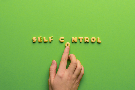 self controt concept, person making words of cookies isolated on green Stock Photo