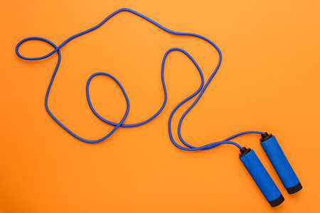 top view of sports jumping rope isolated on orange,
