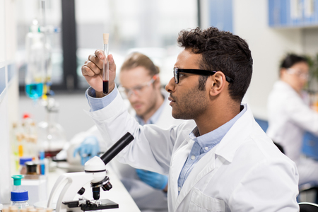 young scientist in eyeglasses looking at test tube in research laboratory
