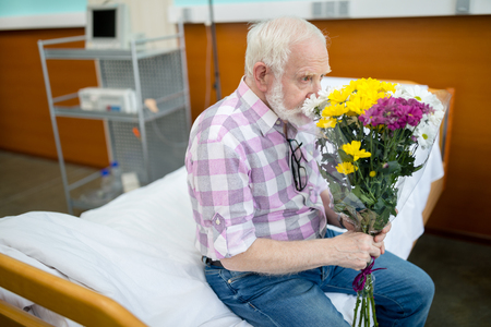 Senior man with flowers in hospital Banco de Imagens