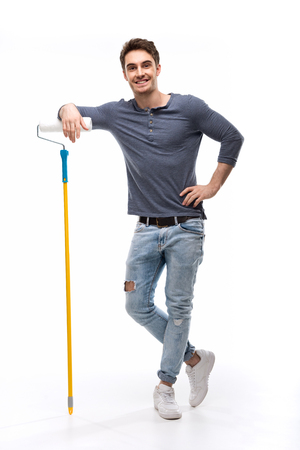 handsome man holding paint roller isolated on white Stock Photo