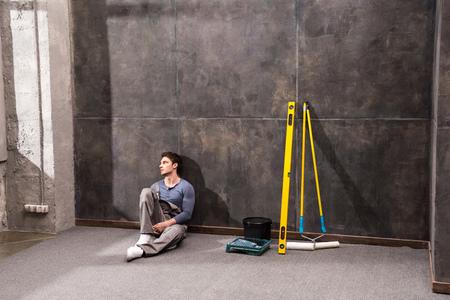 obrero trabajando: Pensive young laborer sitting on floor and looking away