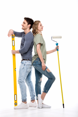 young professional couple holding paint roller and building level isolated on white