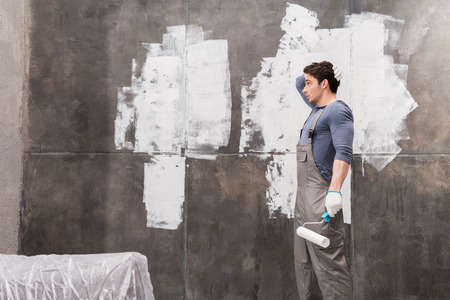 work from home: confused young man with paint roller renovating home