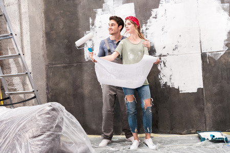 schemes: couple with schemes and paint roller, renovation home concept