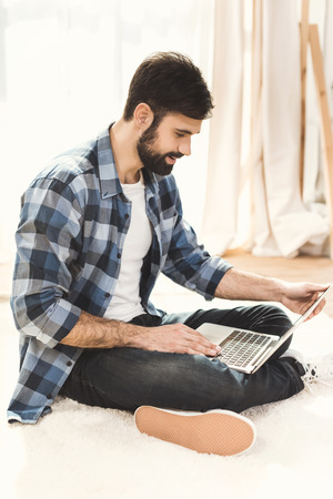 Man sitting on carpet and working on laptop Stock Photo