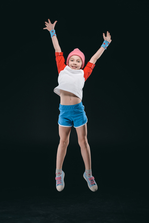 sporty girl jumping isolated on black, activities for children concept Stock Photo