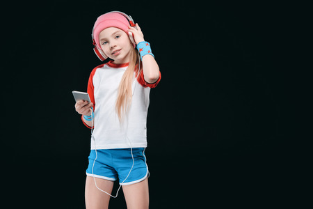Cute sporty girl in headphones using smartphone and smiling at camera