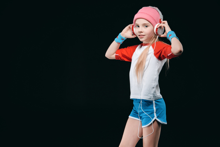 Smiling little girl in sportswear wearing headphones and posing isolated on black Фото со стока
