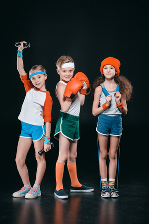 Three active kids in sportswear posing with sport equipment