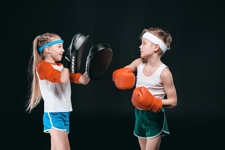 Side view of boy and girl in sportswear boxing isolated on black